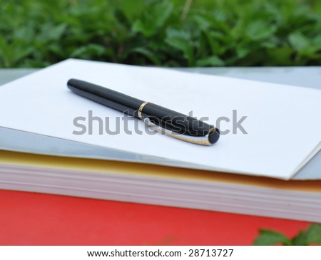 In outdoors lawn pen, card and book