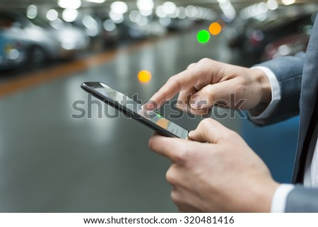 In parking car a man using his cell phone. Close-up hands