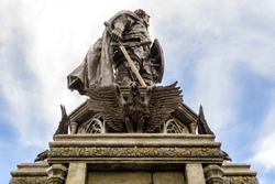 in profile, statue of warrior with sword and shield at the feet of which eagles with outstretched wings, selective focus