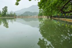 In rainy days, the river and the riverbank provide people with rest, pavilions. Tea fields on the hillside by the bank.