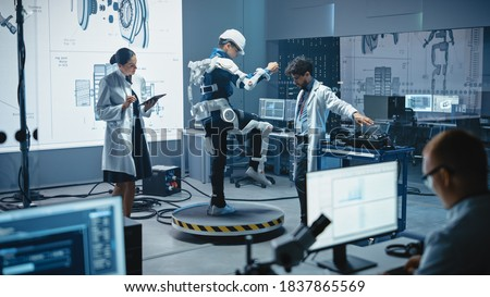 In Robotics Development Laboratory: Engineers and Scientists Work on a Bionics Exoskeleton Prototype with Person Testing it. Designing Wearable Exosuit to Help Disabled People, Warehouse Workers Сток-фото ©