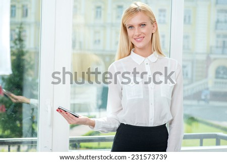 In safe hands. Smiling business woman holding a cell phone in her hand while businessman in formal attire is standing in front of office windows and looking away