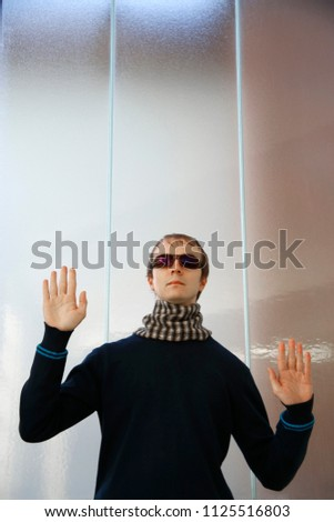 In search of a way. Young man in sunglasses with raised hands behind glass wall. Conceptual photo on the subject of decision making. Metaphor of blindness or moving by touch. Trial and error method.