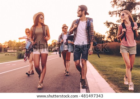 In search of adventures. Group of young people with backpacks walking together by the road and looking happy  #481497343