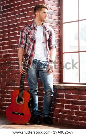 In search of inspiration. Full length of handsome young man holding acoustic guitar and looking through window