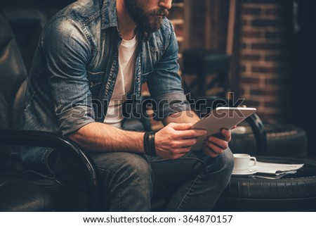 In search of new ideas. Close-up of young bearded man holding digital tablet and sitting in chair