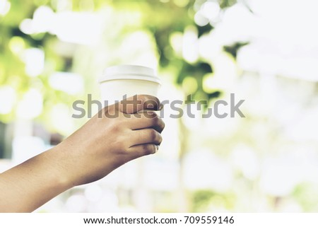 In selective focus of A Cup Of Hot Coffee In Woman Hand Holding Against Blur Green Bokeh Background.Business Travel Outdoor Office Concept.Split tone pinterest,instragram like.Warm Tone With Sun Light #709559146