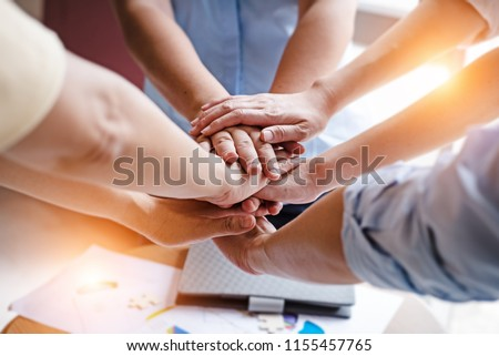 In selective focus of human hands stacked together,Business group,Hands together joining teamwork concepts,Collaborate project,blurry light around.