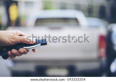 In selective focus of woman Hand presses on the remote control car alarm systems.Cross processing.Auto insurance business.Car security lock  system concept. #593333354
