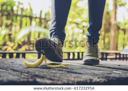 In selective focus of Woman to step on banana skin.People risk concept.Used cross processing to vintage style.