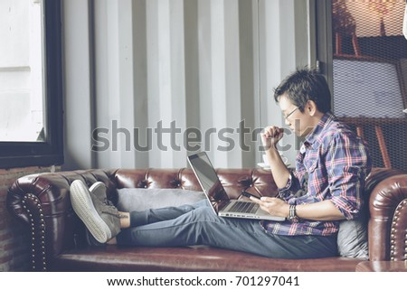 In selective focus to soft focus of Young businessman using tablet computer in classy coffee shop.Interior of coffee shop with customer using digital devices on free wifi internet service. #701297041