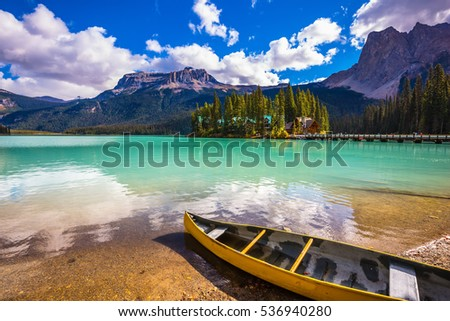 In shallow water the small boat is moored. The concept of eco-tourism and active tourism. The mountain Emerald lake Yoho National Park #536940280