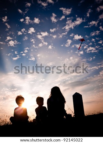 In silhouette, a woman with two young children flying a kite in the sky with a colorful sunset as a backdrop.