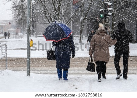 In snowstorm people cross the street. Winter, frost and urban environment Foto stock ©