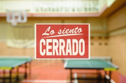 in Spanish inscription sorry we are closed. introducing forbidden measures for attending group classes. Naturally blurred interior of modern gym with tables for ping-pong