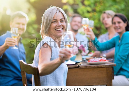 In summer. a group of friends in their forties gathered around a table in the garden to share a meal. They toast with their glasses of wine to the camera.