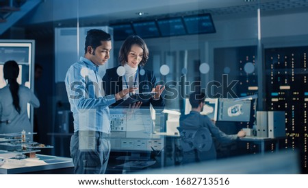 In Technology Research Facility: Female Project Manager Talks With Chief Engineer, they Consult Tablet Computer. Team of Industrial Engineers, Developers Work on Engine Design Using Computers