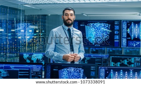 In the Artificial Intelligence Engineering Laboratory Scientist Excitedly Describes Project He's Working on. Background Shows Screens with High-Tech Futuristic Designs.