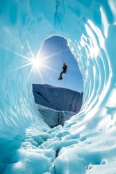 In the backcountry of Alaska, an ice climber rappels into an ice cave on the Matanuska Glacier. The sun shines in the entrance of the blue cavern and reflects off the walls of the smooth ice.