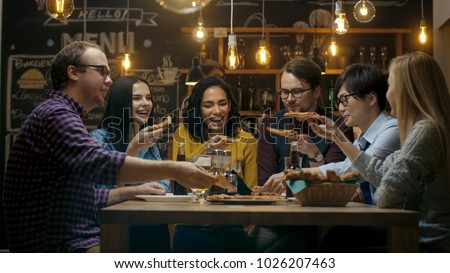 In the Bar/ Restaurant Group of Diverse Young People Eat Slices of Pizza Pie. They Talk, Tell Jokes and Have Fun in This Stylish Establishment. stock photo
