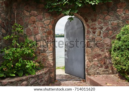 In the beautiful stone wall the iron door is ajar. In the doorway we see a river