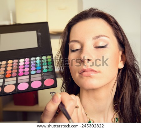 In the beauty salon. Girl doing makeup. Cosmetics and color palette for makeup. Cosmetics, woman, fashion, beauty, care, face, glamor, trend - the concept of a modern lifestyle. Work up artist.