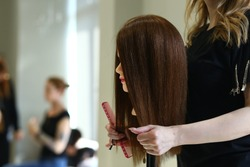 In the beauty salon, hairdressers cut hair to a mannequin. Mannequinhead is a white brunette girl with long hair