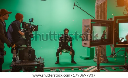 In the Big Film Studio Professional Crew Shooting Blockbuster Movie. Director Commands Camera Operator to Start shooting Green Screen CGI Scene with Actor Wearing Motion Tracking Suit and Head Rig