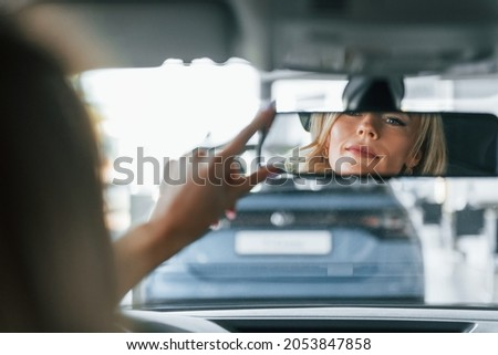 In the car. Woman in formal clothes is indoors in the autosalon.