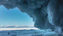 In the cave, rows of fancy blue icicles, similar to lace, hang from the vault of the grotto. The walls are icy. Ahead - a clear azure sky, a snow-covered mountain range, a frozen lake. Baikal.