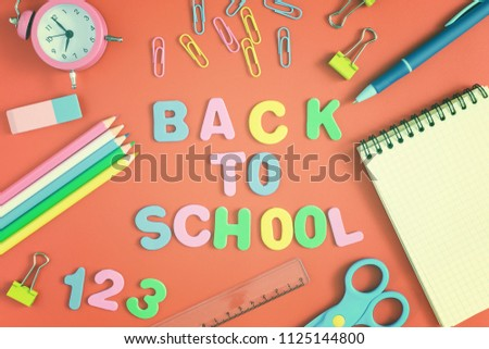 In the center of the brightly orange background is the inscription BACK TO SCHOOL , made in colored letters. Nearby are colorful school and office supplies. Bright layout. #1125144800
