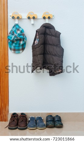 In the children's room on the hanger hangs a jacket and there are d shoes #723011866