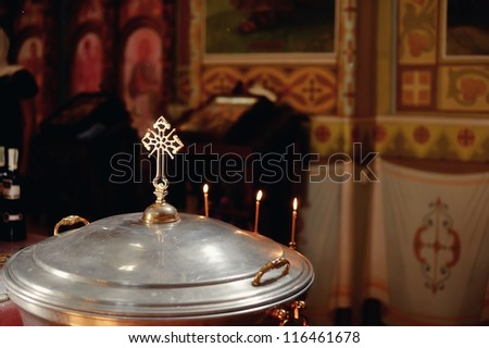 in the church against church paraphernalia candles next to the cross