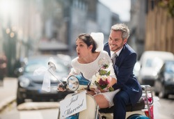 In the city. Newlyweds having fun on a decorated vintage scooter, they are going on honeymoon. There is a signboard just married on the vehicle, scooter led by the bride. Shot with flare