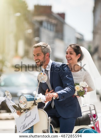 In the city. Newlyweds having fun on a decorated vintage scooter, they go to honeymoon. There is a signboard just married on the vehicle, the bride has her bouquet at hand. Shot with flare Foto stock ©