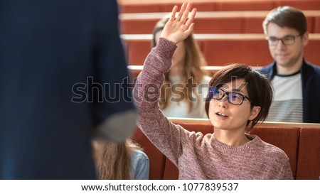 In the Classroom Smart Asian Student Raises Hand and Asks Lecturer a Question. Multi Ethnic Group of Modern Bright Students at the College.