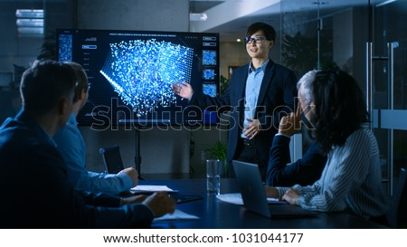 In the Conference Room Chief Engineer Presents to a Board of Scientists New Revolutionary Approach for Developing Artificial Intelligence and Neural Networks. Wall TV Shows Their Achievements.