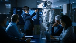 In the Conference Room of the Center of Technology Chief Engineer Presents Next Generation Space Suit to a Board of Directors. Completely Original Design with Integrated AI and Neural Network Systems.