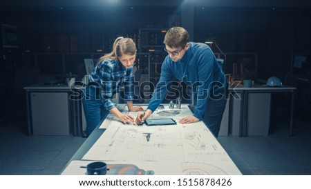 In the Dark Industrial Design Engineering Facility Male and Female Engineers Talk and Work on a Blueprints Using Conference Table. On the Desktop Drawings, Drafts and Electric Engine Components, Parts