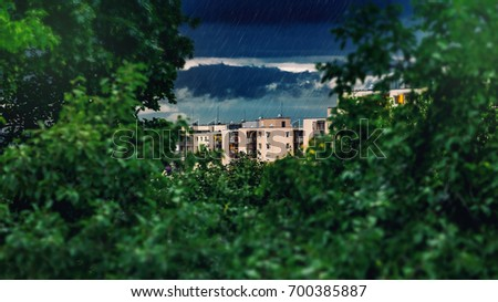 In the distance a thunderstorm is formed, rain falls, green foreground in the foreground #700385887