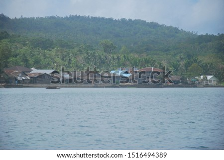 in the distance there is a fishing village in Kei Island in Maluku, Indonesia. most of the people on the coast of Maluku have livelihoods as fishermen