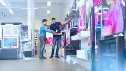 In the Electronics Store Professional Consultant Shows Latest TV's to a Young Man, They Talk about Specifications and What Model is Best for Young Man's Home. Store is Bright and Has Latest Models.