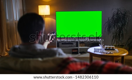 In the Evening Back View of a Middle Aged Man Sitting on a Couch Watching Big Flat Screen TV, He Switches Channels with Remote Control. It's Evening.