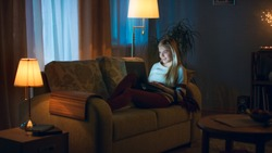 In the Evening Beautiful Young Woman Lies on the Couch with a Laptop on Her Knees. She Types and has Fun. Room Looks Warm and Cozy.