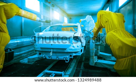In the factory of automobile manufacturing, the automatic painting robot arm is spraying the body paint surface.
