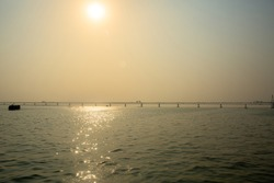 In the foggy afternoon, the under-construction PADMA Multipurpose Bridge can be seen on the river Padma. The reflection of sunlight is glistening in the river water.
