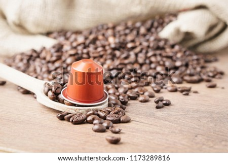 In the foreground a coffee capsule on wooden spoon and   roasted coffee beans with burlap sack on blur wooden background ,close up. #1173289816