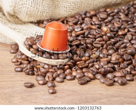 In the foreground a coffee capsule on wooden spoon and   roasted coffee beans with burlap sack on blur wooden background ,close up. #1203132763