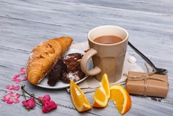 In the foreground a croissant with a chocolate cake and an orange on a gray wooden background, a number of pink petals are next to it, a free space for text.