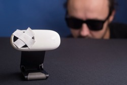 in the foreground a webcam sealed with adhesive tape, in the background a man in black glasses is watching a caller on another line. Privacy tracking concept